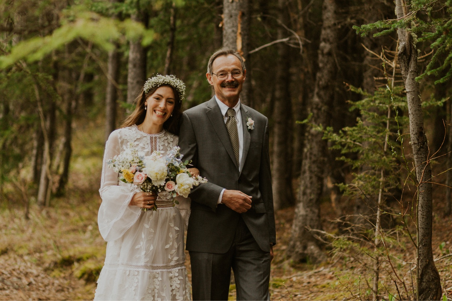 A Kananaskis Lake Elopement in the beautiful Canadian Rockies photo of bride walking down the forest with her dad