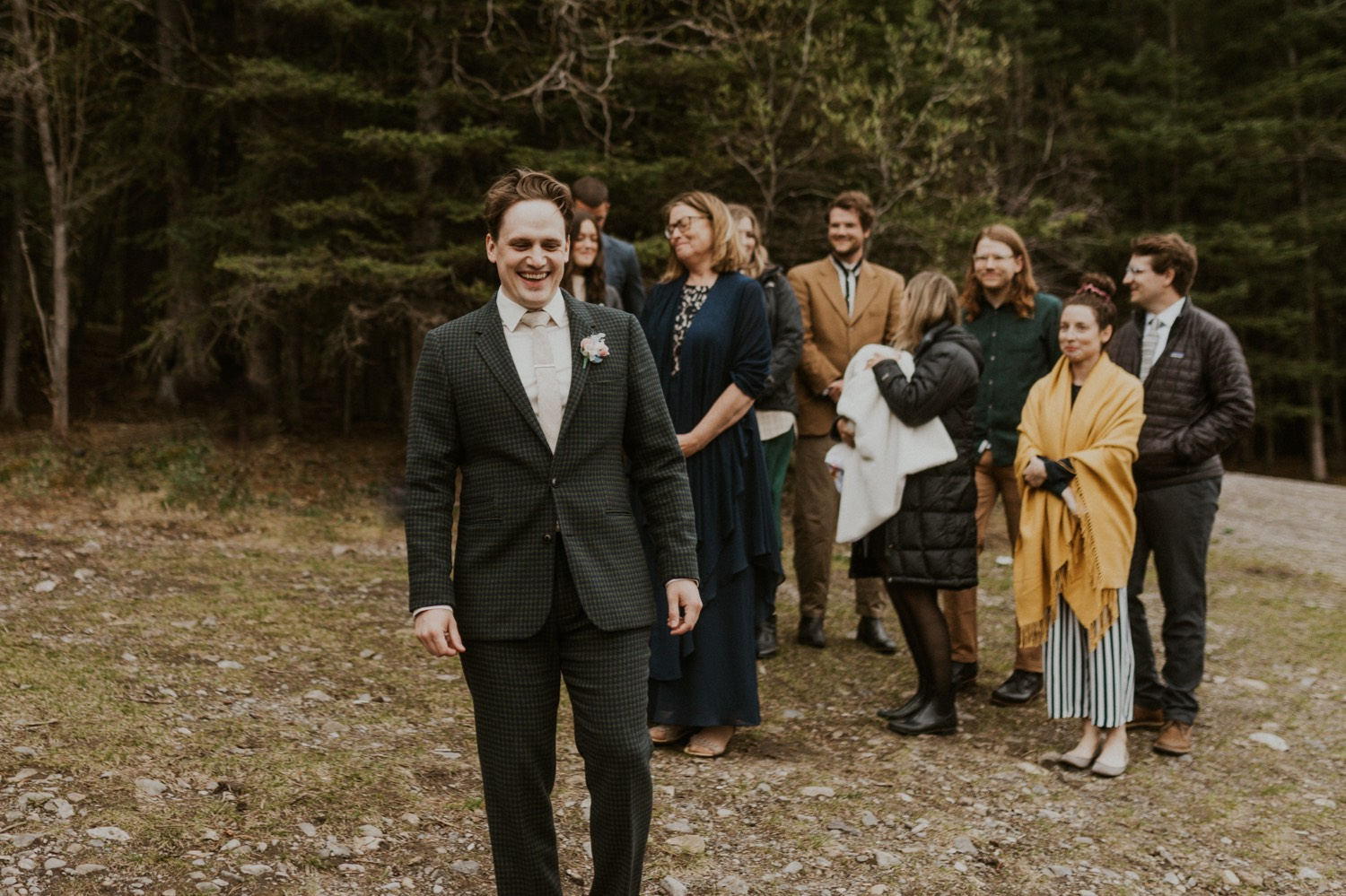 A Kananaskis Lake Elopement in the beautiful Canadian Rockies photo of groom walking down to ceremony spot