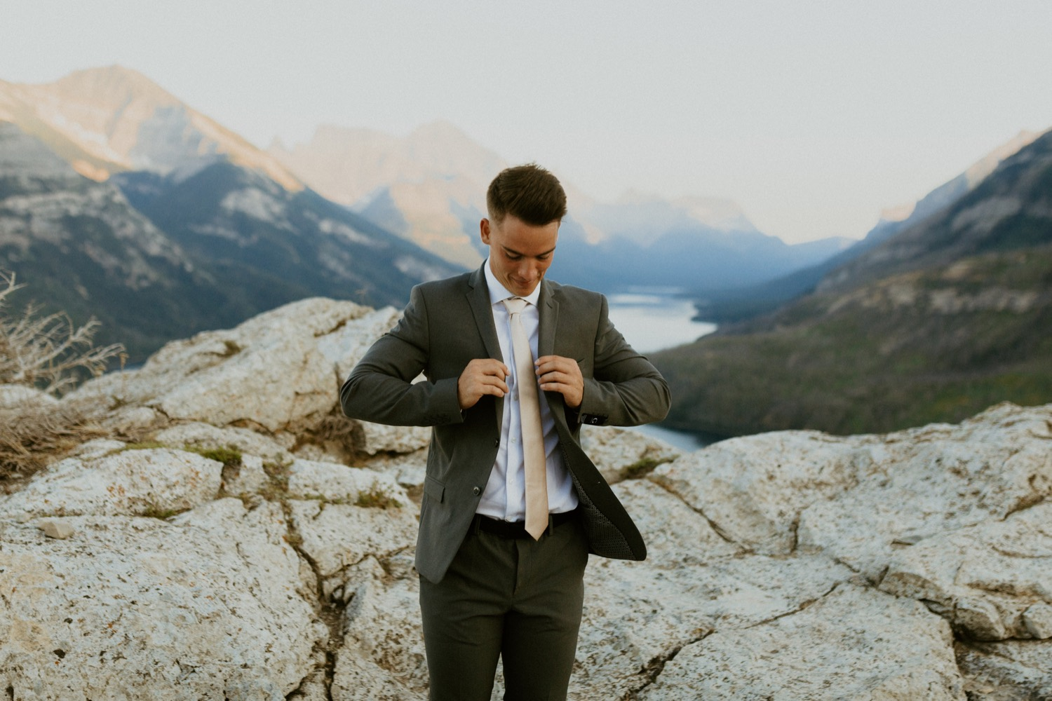 Waterton Wedding Adventurous Mountain Elopement style in the beautiful Canadian Rocky Mountains groom fixing his tie on the mountain top