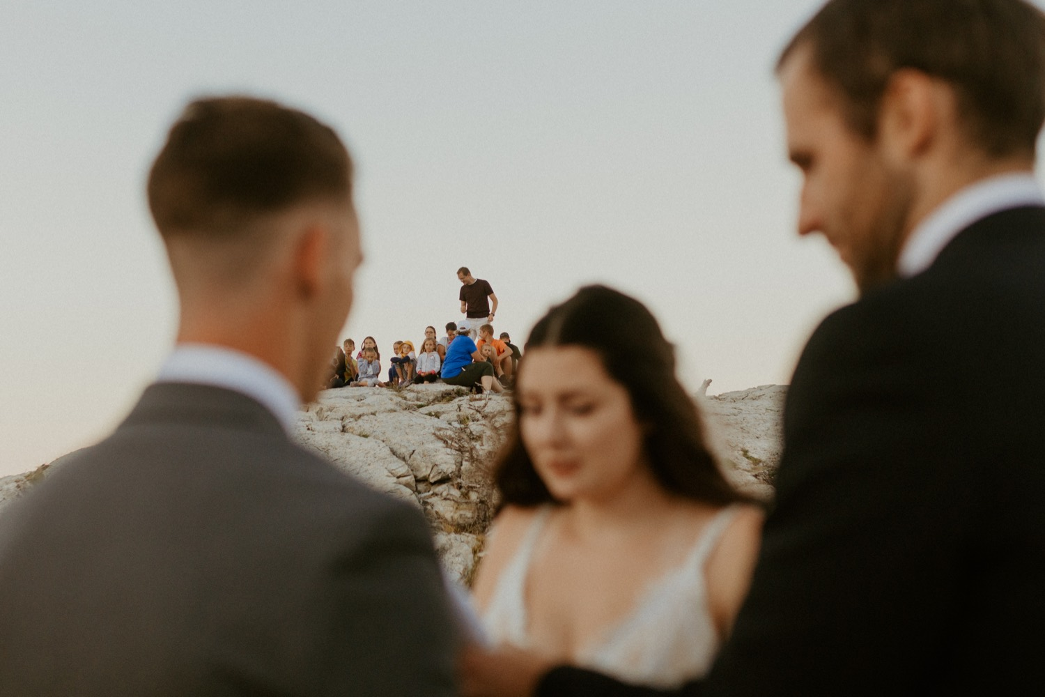 Waterton Wedding Adventurous Mountain Elopement style in the beautiful Canadian Rocky Mountains ceremony at the mountain top with close friends and officiant with crowd watching from behind